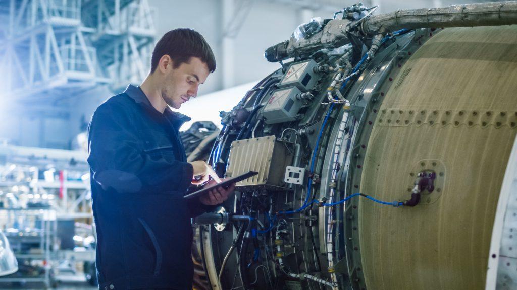 Ein Arbeiter steht vor einer Flugzeugturbine im Hangar