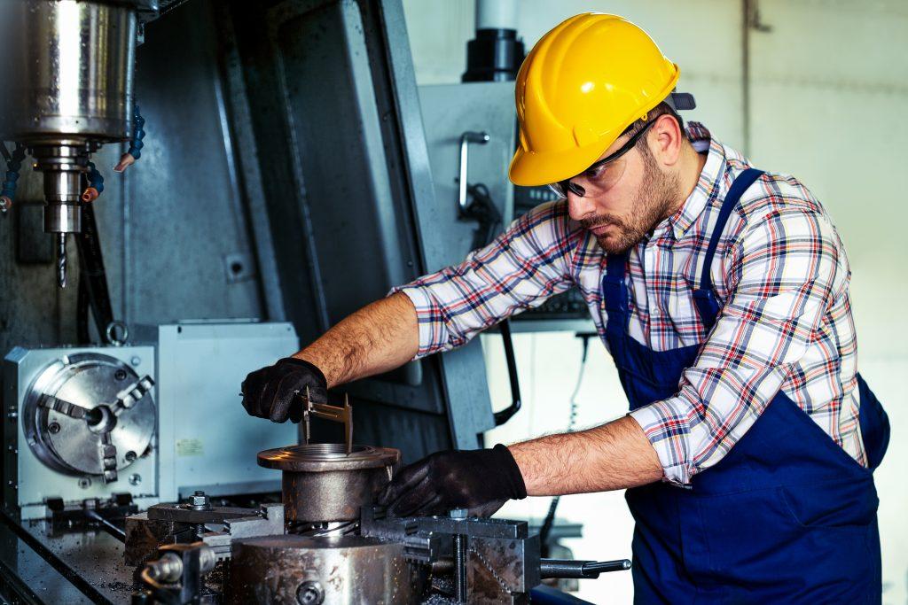 Arbeiter prüft ein Bauteil an einer Maschine