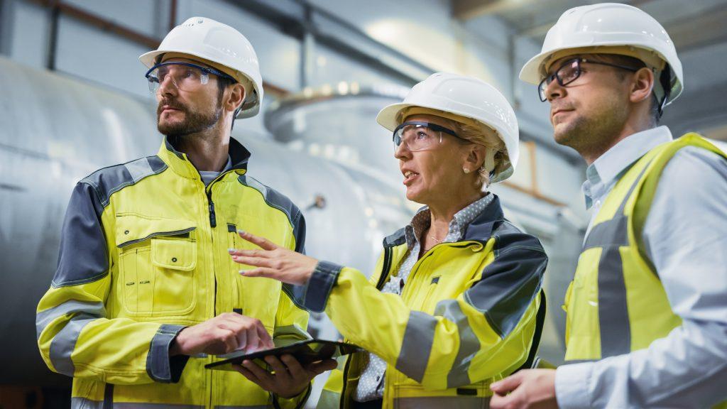 Drei Mitarbeiter diskutieren in einer Produktionsstätte