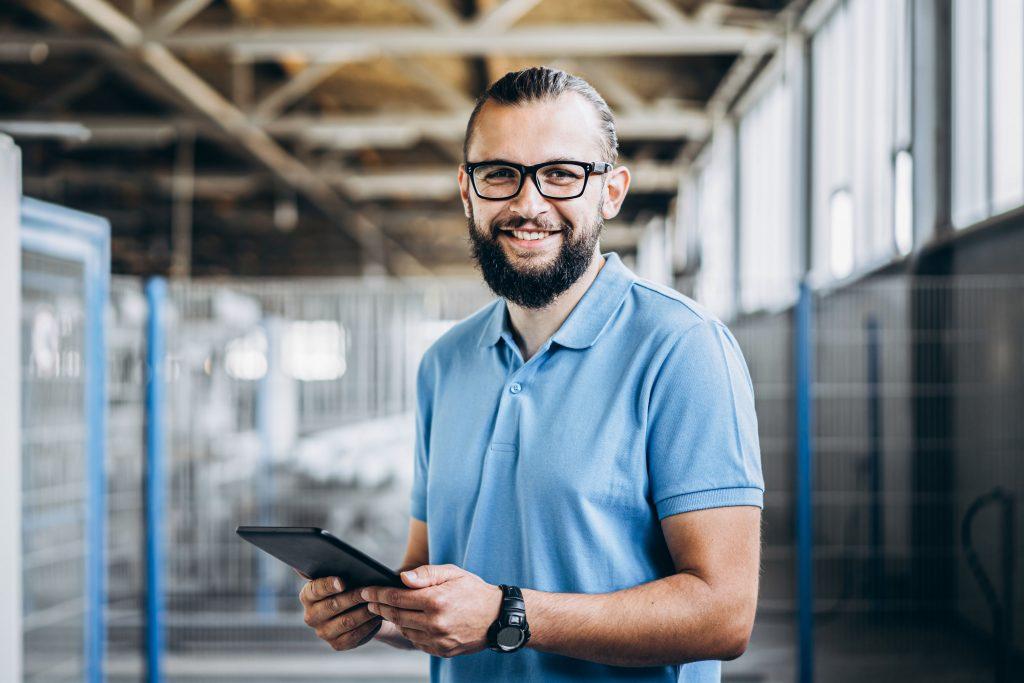 Ein Arbeiter lächelt in die Kamera und hält ein Tablet in der Hand