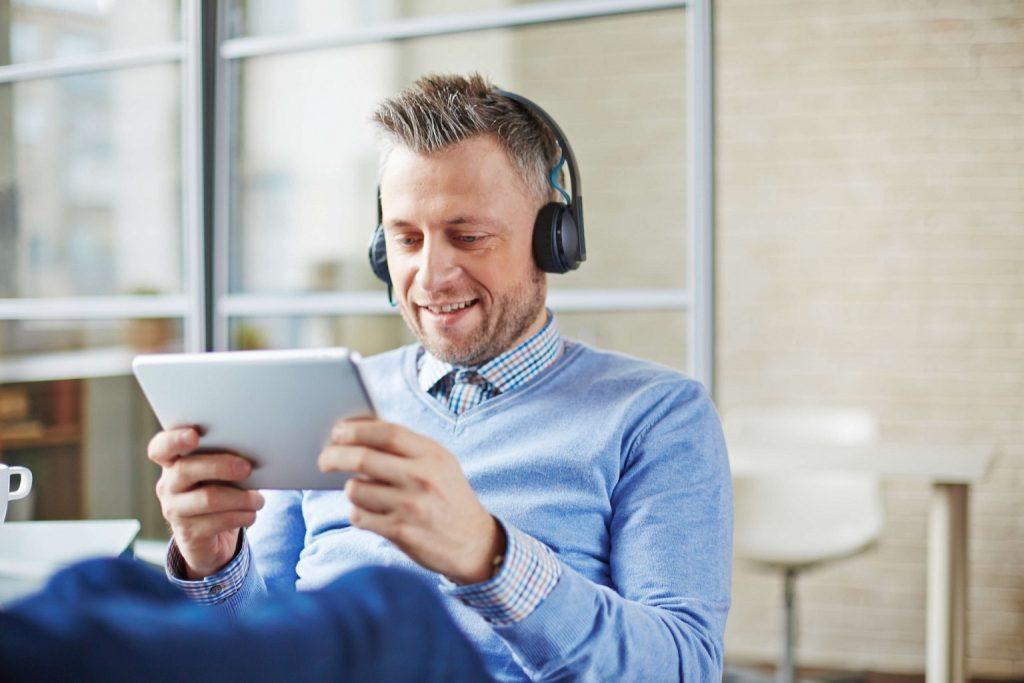Mann mit Kopfhörern schaut auf ein Tablet