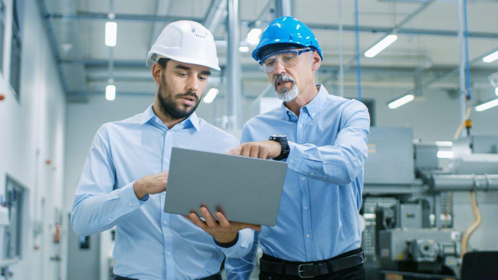 Projekt Manager und Ingenieur diskutieren am Laptop